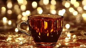 Bubbles on the surface of hot freshly brewed black tea. Drink is poured into small transparent glass cup, small gold lights, mag reflects lights, garland on stock video footage