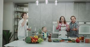 Bubbles time in the kitchen a family spending time together making bubbles and playing funny all together. 4k stock footage