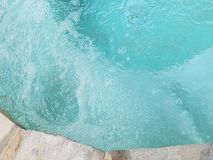Bubbles in the turqoise water of a hot tub with rock rim top view stock photography