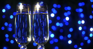 Bubbling champagne being poured into two crystal glasses against black. 4k stock footage