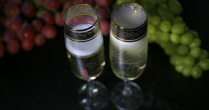 Bubbling champagne being poured into two crystal glasses against boke black backgroung. Bubbling champagne being poured into two crystal glasses against boke stock video footage