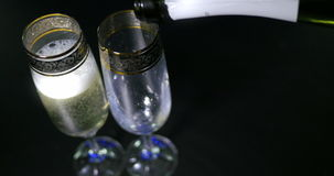 Bubbling champagne being poured into two crystal glasses against boke black backgroung. Bubbling champagne being poured into two crystal glasses against boke stock video