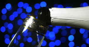 Bubbling champagne being poured into two crystal glasses against boke black backgroung. Bubbling champagne being poured into two crystal glasses against boke stock footage