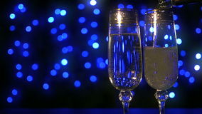 Bubbling champagne being poured into two crystal glasses against boke black backgroung. 96fps stock footage