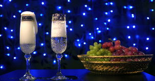 Bubbling champagne being poured into two crystal glasses against boke black backgroung. 4k stock video footage