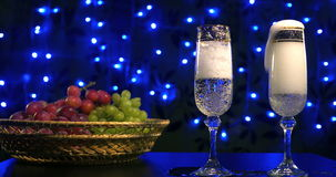 Bubbling champagne being poured into two crystal glasses against boke black backgroung stock video