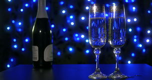 Bubbling champagne being poured into two crystal glasses against boke black backgroung. 4k stock footage
