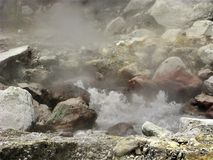 Bubbling hot spring between rocks at Furnas on Sao Miguel, The Azores. Bubbling hot spring with steam amongst rocks at Furnas on Sao Miguel island, The Azores stock photography