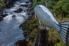 The bubbling Ketchikan Creek runs passed a sculpture of a salmon royalty free stock photography