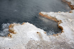Bubbling Shoreline. This was a hot spring at Yellowstone National Park that probably contained sulfur due to the yellow hue around the pool. It was hot enough to Royalty Free Stock Images