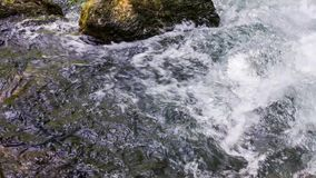 Bubbling Water Of Mountain River Flowing Down. Tracking close up shot of a bubbling water with foam of mountain river flowing down fast among stones. The shot stock video footage
