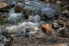 Bubbling water stream of the mountain river close up Stock Image