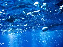 Bubblor från en dykare som stiger till yttersidan i det blåa havet royaltyfri bild
