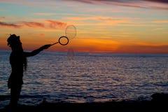 Bubblor silhouetted av solnedgången av San Antonio Bay i Ibiza, Spanien royaltyfria bilder