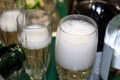 Bubblor som är kommande av hälld champagne i ett skummande exponeringsglas med omgeende flaskformer och mer champagne som hälls Royaltyfria Bilder