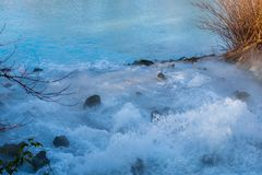Bubbly introduction of turquoise mine water into a pond. In Bochum royalty free stock photography