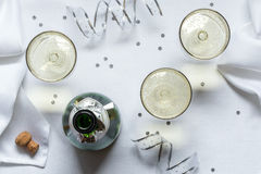 Bubbly. An uncorked bottle of bubbly with 3 filled champagne coupes in a festive setting stock photography