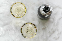Bubbly. An uncorked bottle of bubbly with two hand blown coupes nestled curly ribbon stock photography