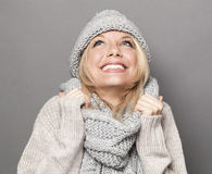 Bubbly young blonde woman smiling for warmth and cozyness in winter Stock Photography