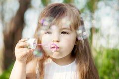 Bubles del jabón de la muchacha que soplan Imagenes de archivo