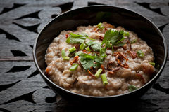 Bubur Lambuk. Traditional homemade Bubur Lambuk congee porridge in black bowl on wooden carving top stock photography