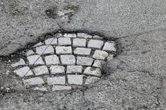 Buca con vecchia pavimentazione di pietra grigia fotografia stock