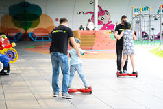 BUCAREST, RUMANIA, - 2 de abril de 2016: Gente que usa el hoverboard, tablero de dos ruedas de uno mismo-equilibrio, en el parque Foto de archivo libre de regalías