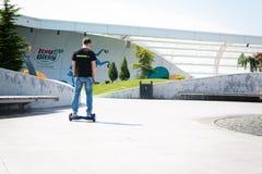 BUCAREST, RUMANIA, - 2 de abril de 2016: Gente que usa el hoverboard, tablero de dos ruedas de uno mismo-equilibrio, en el parque Foto de archivo