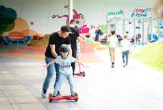 BUCAREST, RUMANIA, - 2 de abril de 2016: Gente que usa el hoverboard, tablero de dos ruedas de uno mismo-equilibrio, en el parque Imagen de archivo