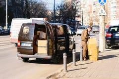 Bucareste, Romênia - 25 de janeiro de 2018: Trabalhador de UPS que entrega pacotes A camionete de UPS encheu-se com o pronto para Imagem de Stock Royalty Free