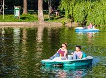 Bucareste, Rom?nia - 2019 Amigos novos que falam quando esporte de barco do pedal no lago Amigos alegres que relaxam no barco do  imagem de stock