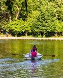 Bucareste, Rom?nia - 2019 Família que relaxa no barco de fileira no dia ensolarado quente no lago gardens de Cismigiu imagem de stock
