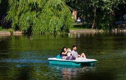 Bucareste, Rom?nia - 2019 Família que relaxa no barco do pedal no dia ensolarado quente no lago gardens de Cismigiu fotos de stock royalty free
