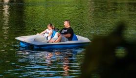 Bucareste, Rom?nia - 2019 Família que relaxa no barco do pedal no dia ensolarado quente no lago gardens de Cismigiu imagens de stock royalty free