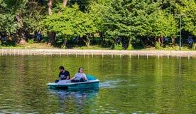 Bucareste, Rom?nia - 2019 Pares novos que falam ao lado do lago garden de Cismigiu em Bucareste fotografia de stock royalty free