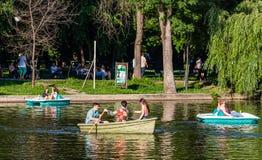 Bucareste, Rom?nia - 2019 Povos que relaxam no barco do pedal no dia ensolarado quente no lago gardens de Cismigiu fotografia de stock royalty free