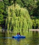 Bucareste, Rom?nia - 2019 Retrato de pares novos no amor que fala quando esporte de barco do pedal no lago Homem e mulher alegres imagem de stock