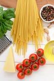 Bucatini crudo con los ingredientes para la receta de las pastas en la tabla de madera blanca Fotos de archivo libres de regalías