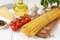 Bucatini de las pastas con los tomates, el ajo, el queso y el aceite en el fondo de madera blanco Foto de archivo libre de regalías