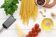 Bucatini italiano de las pastas con los tomates, la albahaca, el aceite, el ajo y el queso en la tabla de madera blanca Fotos de archivo