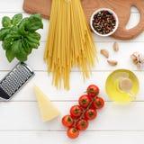 Bucatini o espaguetis secos de las pastas con la albahaca, aceite, queso, tomates en el fondo de madera blanco Imágenes de archivo libres de regalías