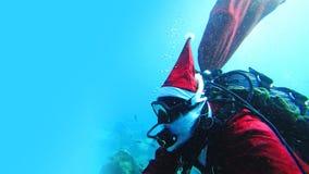 Buceador de Santa Claus Scuba con el bolso rojo de la Navidad que nada bajo el agua imagen de archivo