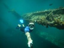 Buceador gratuito que toma el selfie con la nave hundida en fondo foto de archivo libre de regalías
