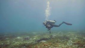 Buceador que flota en la parte inferior de mar y la mano que agita a la cámara, visión subacuática almacen de metraje de vídeo