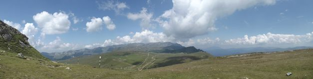 Panoramic view from the top of the Bucegi mountains under a few clouds trying to block the summer sun. The Bucegi is believed to be the Dacian holy mountain royalty free stock images