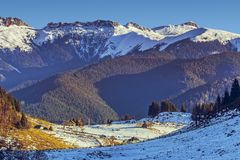 Bucegi mountains, Fundata, Romania. Sunny winter morning landscape with Bucegi mountains range and scattered ancient houses or farms in the valley, Fundata stock photos