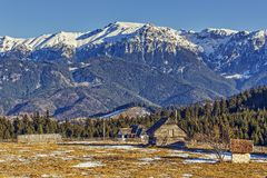 Bucegi mountains landscape, Romania. Winter rural landscape with snowy Bucegi mountains ridge, meadow enclosure and wooden barn in Fundata village, Brasov county royalty free stock photos
