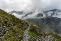 Bucegi Mountains peaks. View from a grass and rock slope of clouds and peaks in the Bucegi Mountains in Romania, located in the Southern Carpathians group of the stock photography