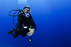 Buceo con escafandra en agua azul clara Foto de archivo