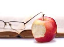 Buch, Apfel und Gläser Stockfotografie